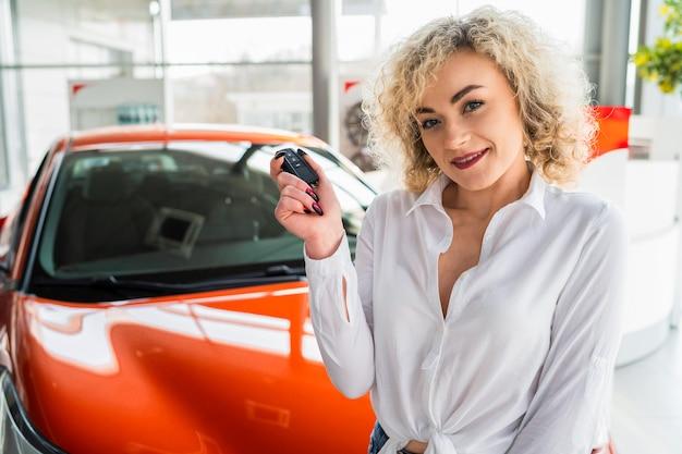 Frau mit schlüssel in den händen nahe auto