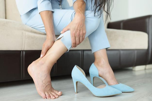 Frau mit schmerzhaften empfindungen in den beinen sitzt mit ausgezogenen schuhen auf der couch