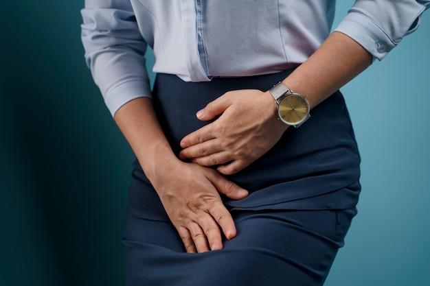 Frau mit schmerzhaften händchenhalten, die ihren schritt unterbauch drücken