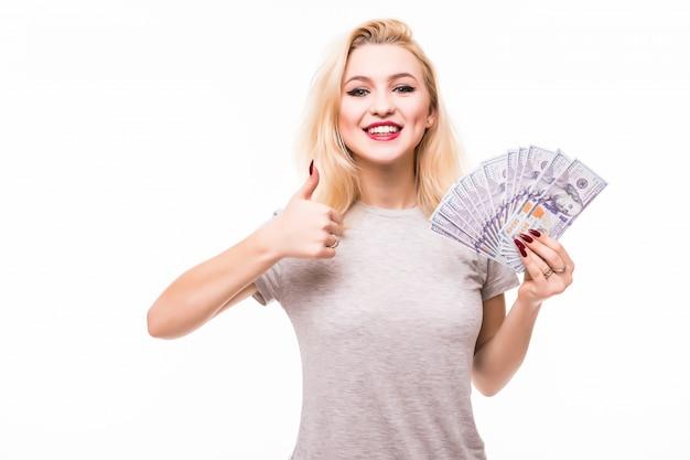 Frau mit schönem gesicht und körper, die handfächer von banknoten auf weißer wand hält