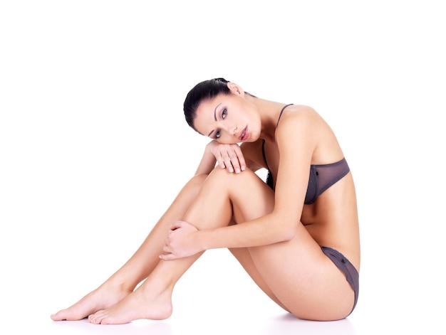 Frau mit schönen beinen im bikini sitzt auf weißer wand