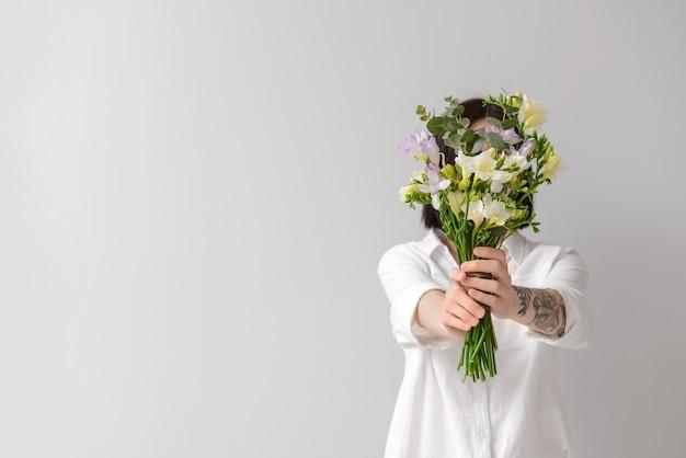 Frau mit schönen freesienblumen auf heller oberfläche