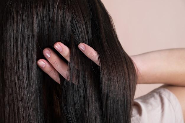 Frau mit schönen langen haaren auf beigem hintergrund