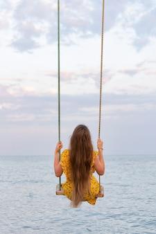 Frau mit schönen langen haaren sitzt auf schaukel auf seehintergrund.