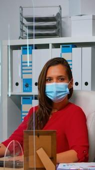 Frau mit schutzmaske arbeitet und schaut in die kamera, die vor dem pc sitzt. mitarbeiter im arbeitsbereich eines unternehmens, die auf der computertastatur tippen und auf den desktop schauen, um die soziale distanzierung zu respektieren