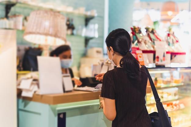 Frau mit schutzmaske, die rechnung am kassenschalter zahlt.