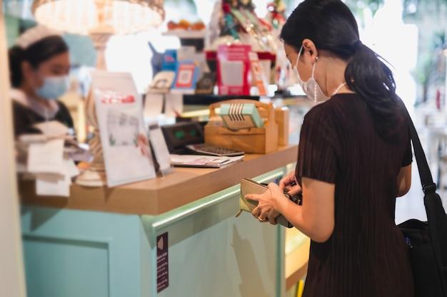 Frau mit schutzmaske, die rechnung am kassierertisch im restaurant zahlt.