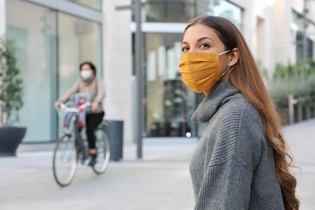 Frau mit schutzmaske schaut sich um und sitzt auf einer bank und wartet auf bessere zeiten in der modernen stadt