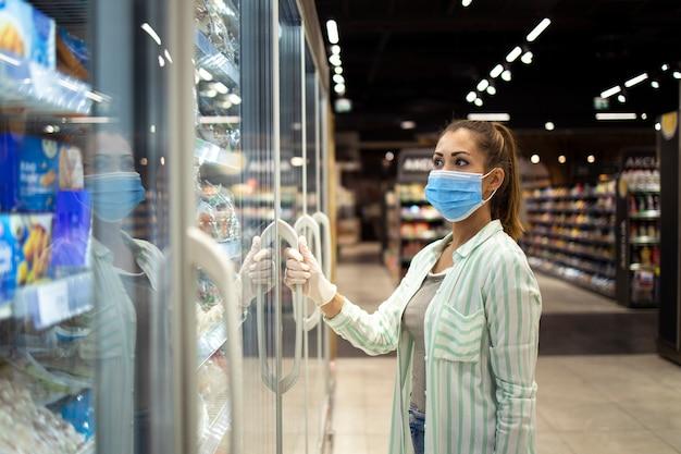 Frau mit schutzmaske und handschuhen, die gefrierschrank im supermarkt während der covid-19-pandemie oder des corona-virus öffnen