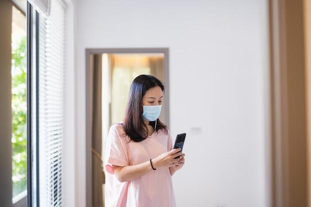Frau mit schutzmaske unter verwendung des handys im haus.