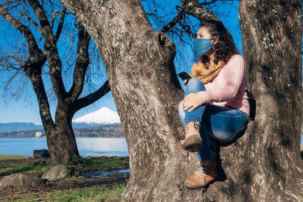 Frau mit schutzmaske unter verwendung des smartphones