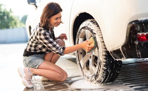 Frau mit schwamm für auto-reinigung auf selbstbedienungs-autowäsche