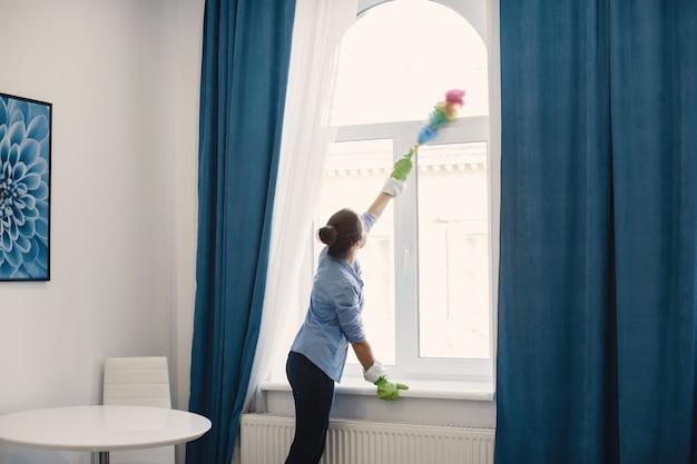 Frau mit schwamm und gummihandschuhen, die haus reinigen