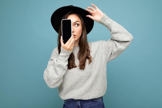 Frau mit schwarzem hut und grauem pullover mit handy mit smartphone isoliert auf
