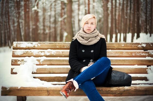 Frau mit schwarzem mantel mit schnee auf einer bank sitzen