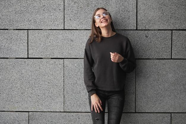 Frau mit schwarzem sweatshirt oder hoodie für mock-up, logo-designs oder designdrucke mit freiem platz auf den straßen der stadt.