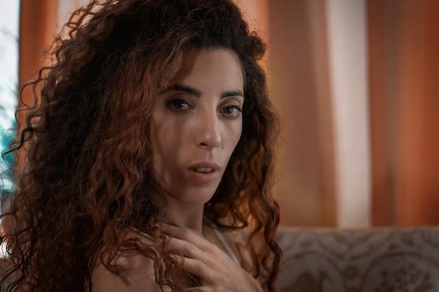 Frau mit schwarzen lockigen haaren in einem raum