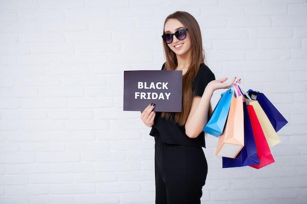 Frau mit schwarzer freitag inschrift und einkaufstüten