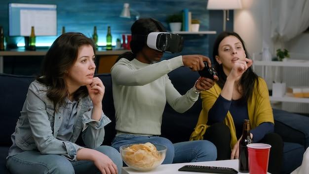 Frau mit schwarzer haut, die ein vr-headset-gaming-spiel für online-wettbewerb mit joystick trägt. gemischte rassengruppe von freunden, die zusammen hängen und bier trinken und spät in der nacht im wohnzimmer spaß haben?