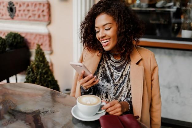 Frau mit schwarzer haut und offenem lächeln, das per telefon spricht