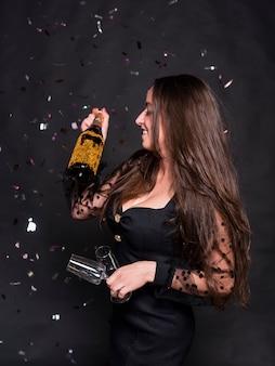 Frau mit sektflasche und -gläsern unter flitter