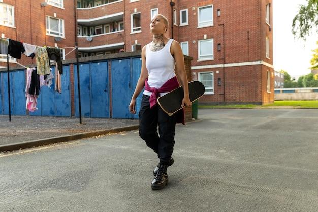 Frau mit skateboard in vororten voller schuss