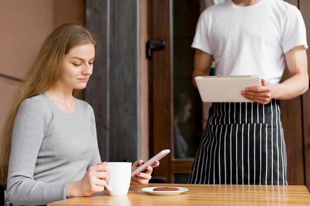 Frau mit smartphone, die kaffee bestellt