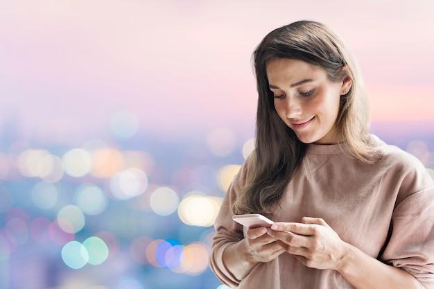 Frau mit smartphone-hintergrund in der neuen normalität mit bokeh-lichtern remixed media