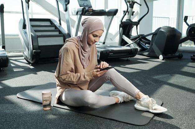 Frau mit smartphone im fitnessstudio