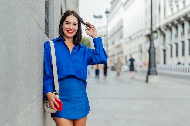 Frau mit smartphone in der hand betrachtet kamera auf der straße