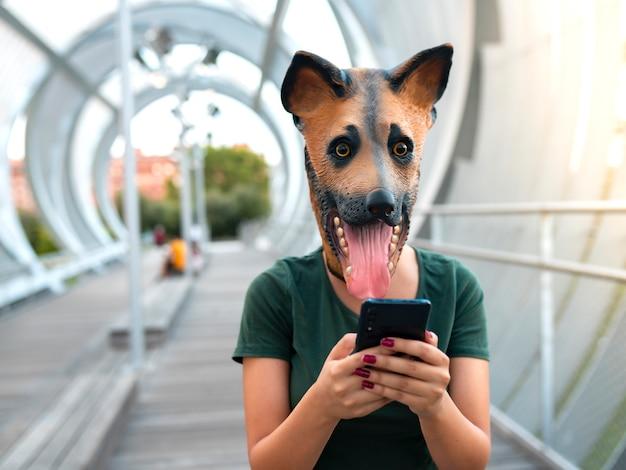 Frau mit smartphone, mit hundemaske