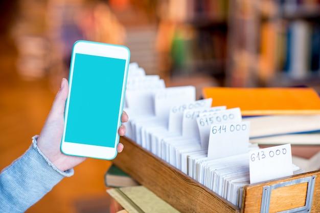 Frau mit smartphone mit leerem bildschirm in der nähe des kartenkatalogs in der bibliothek