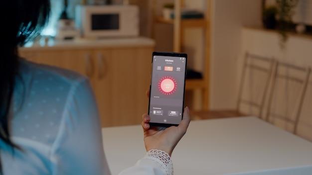 Frau mit smartphone mit lichtsteuerungsanwendung