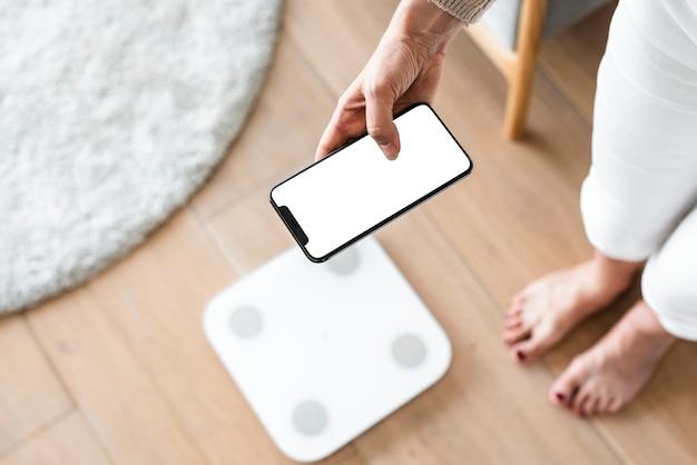 Frau mit smartphone neben waage innovative technologie