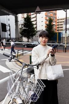 Frau mit smartphone und elektrofahrrad in der stadt