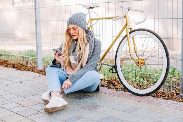 Frau mit smartphone und fahrrad auf pflasterung