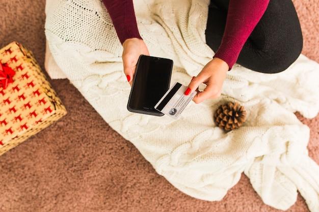 Frau mit smartphone und plastikkarte nahe baumstumpf und geschenkbox
