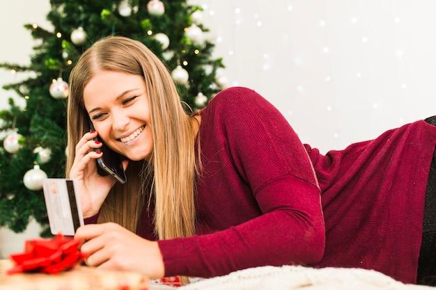Frau mit smartphone und plastikkarte nahe weihnachtsbaum