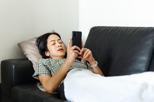 Frau mit smartphone, während sie auf dem couch-quarantäne-konzept liegt