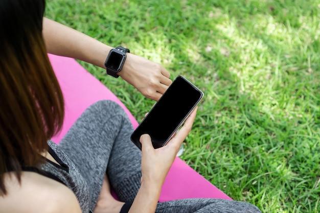 Frau mit smartwatch und telefon beim yoga