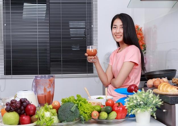 Frau mit smoothies im glas am küchenraum
