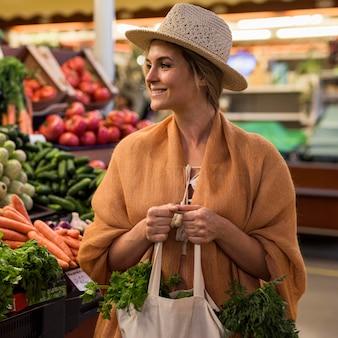 Frau mit sommerhut am marktplatz