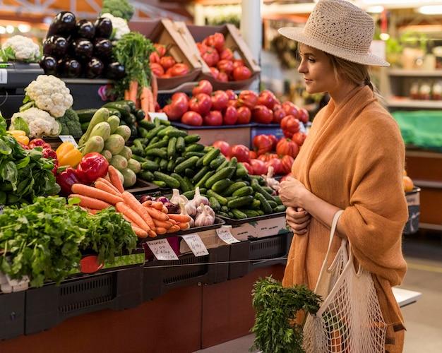 Frau mit sommerhut, die gesundes essen kauft