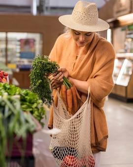 Frau mit sommerhut, die produkte kauft