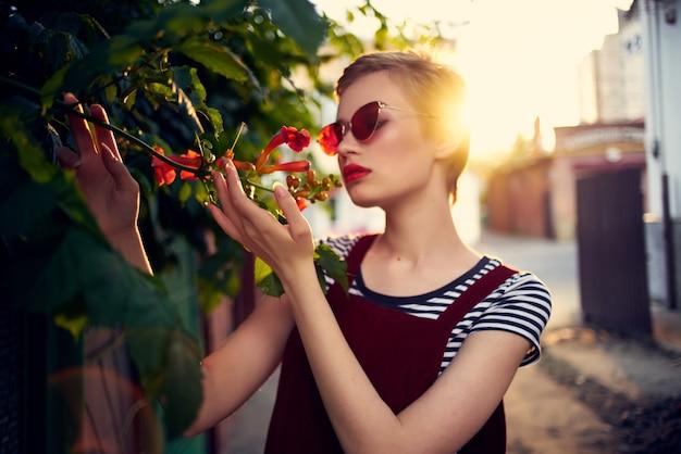 Frau mit sonnenbrille auf der straße in der nähe von blumen, die lebensstil aufwerfen