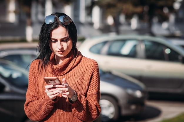 Frau mit sonnenbrille benutzen mobilen smartphone in der stadtstraße.