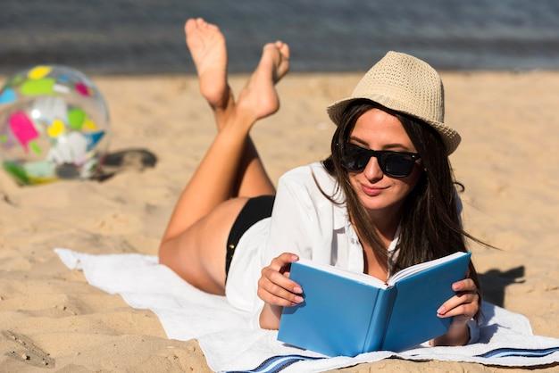 Frau mit sonnenbrille, die ein buch am strand liest
