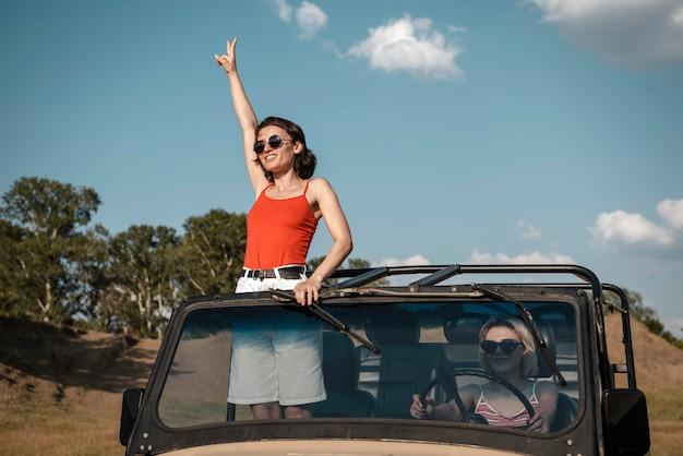 Frau mit sonnenbrille, die spaß beim reisen mit dem auto hat