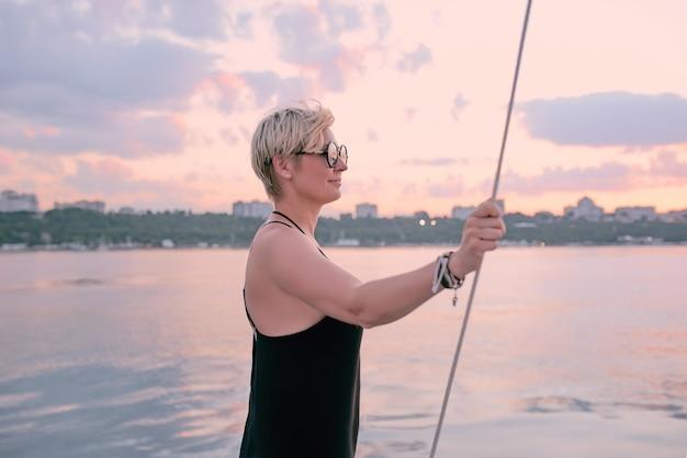 Frau mit sonnenbrille und langem schwarzem kleid, die den sonnenuntergang auf der yacht im meer genießt