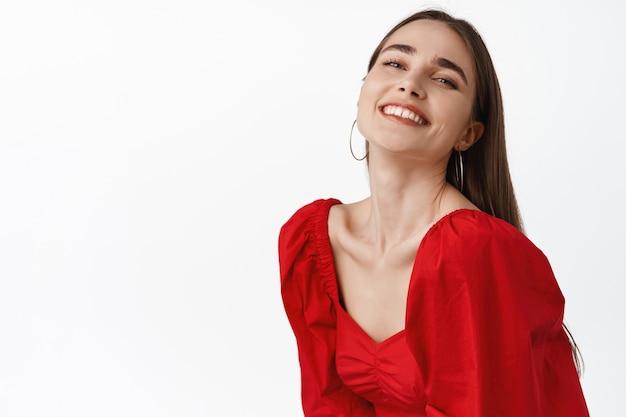 Frau mit sorglosem weißem lächeln, romantisches date genießen, perfekter abend ausgehen, rotes kleid tragen, tanzen und fröhlich auf weiß aussehen.